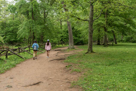 Mother with pink sweater and teen daughter walking down path in Great Falls national Park, Virginia