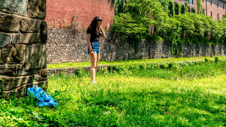 Teen girl standing in grass with blue shorts and black blouse looking down next to Chesapeake and Ohio Canal