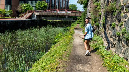 Woman walking down canal toepath in Georgetown, DC turning around to look at the camera