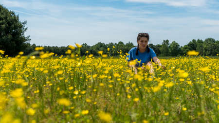 Low angle view of teen girl sitting in large field with yellow flowers and trees in the background