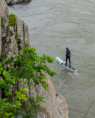man standing on kayak and paddling at Great Falls National Park, Virginia