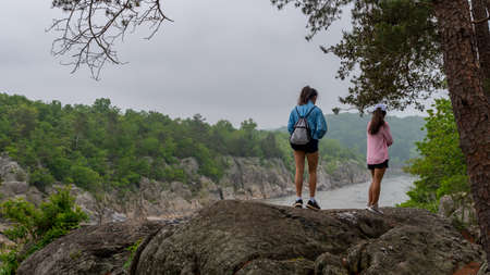 Mother with pink sweater and teen daughter standing on ridge on path in Great Falls national Park, Virginia