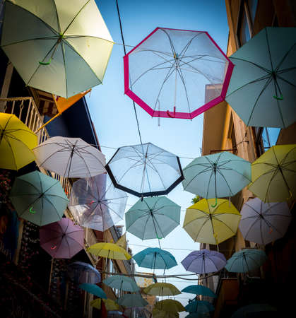 Series of multi-colored umbrellas hanging above the street in Athens Greece Banco de Imagens
