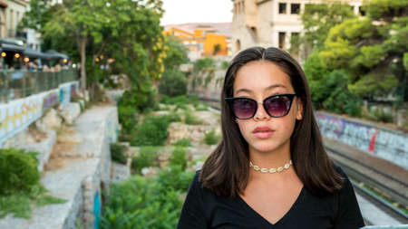 Portrait young Asian teen with sunglasses posing for camera in Athens, Greece