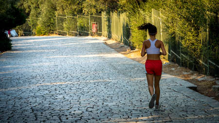 Teen in red shorts and white tanktop jogging on cobblestone road in Athens Greece Reklamní fotografie