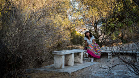 Asian woman in white t-shirt in Athens in white hat, sitting on marble bench in garden on Phillippas Hill