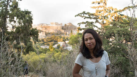Asian woman in white t-shirt in Athens standing in front of Acropolis on Philippapas Hill
