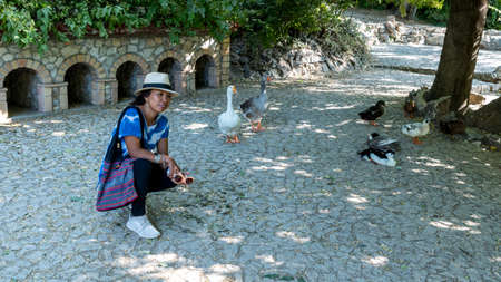 Asian woman with fedora and sunglasses kneeling in front of ducks and geese and looking at photographer in National Gardens in Athens Greece Stock fotó