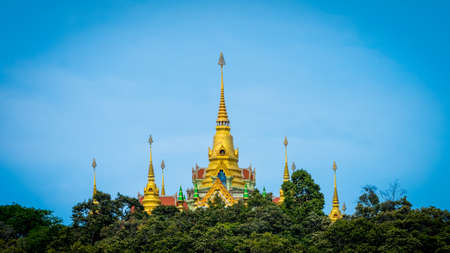 Thai temple rising above the trees with clear blue skies in Ben Krut Thailand