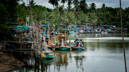 Thai fishing boats tied up to each other in the harbor of Ben Krut with reflections in the water Stok Fotoğraf