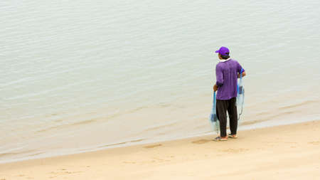 Thai fisherman at the water's edge with blue net at low tide wearing purple hat and shirt with blue net