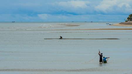 Two fishermen standing in the water at low tide fisihing with a net at beach in Pak nam Pran, Pranburi Thailand Reklamní fotografie