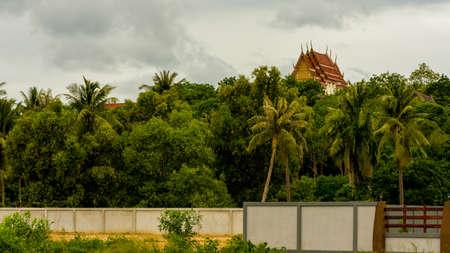 Thai temple rising above the trees and wall in Pak Nam Pran, Pranburi Thailand
