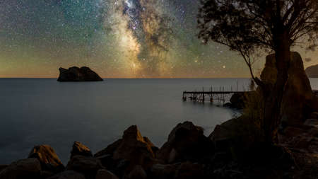 dilapidated,  rundown pier with island in the background on a starry night in Erresos, Lesvos, Greece