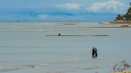 Two fishermen standing in the water at low tide fisihing with a net in Pak Nam Pran Thailand Reklamní fotografie