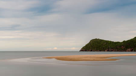 Sand bar sticking our of water at low tide with mountain behind it in Prak Nam Pran Thailand