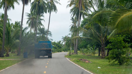 Blue dump truck driving thourgh Thai forest leaving trail of black smoke in Pranburi Thailand Reklamní fotografie