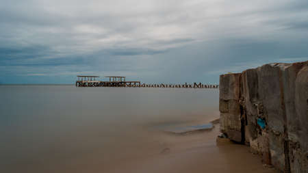closeup of sea wall in front of Dilapidated old fishing dock collapsing into the sea in Pak Nam Pran on the Gulf of Thailand in Thailand