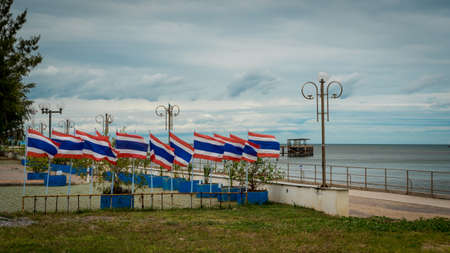 Many flags on poles in a seaside park in Prak nam pran Thailand