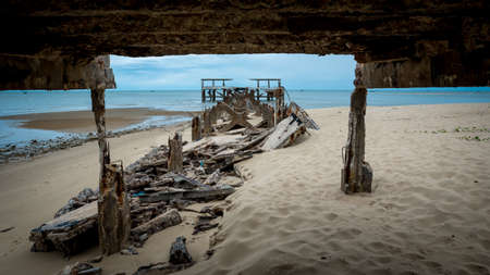Dilapidated old fishing dock collapsing into the sea framed by dock in Pak Nam Pran on the Gulf of Thailand in Thailand