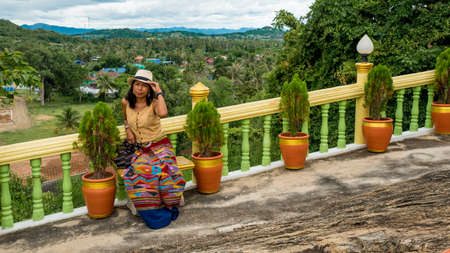Woman standing in garden in wat in Pak Nam pran surrounded by potted plants with clouds in the background Reklamní fotografie