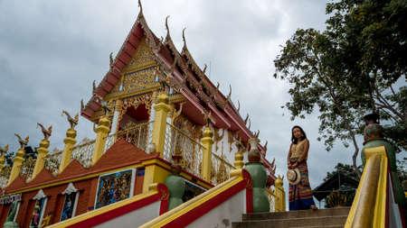 Woman in sarong holding hat in front of a Thai Temple in Pak Nam Pran, Pranburi Thailand