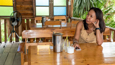 Woman sitting at table in cafe holding cell phone with head propped on hand in Pak Nam Pran, pranburi Thailand