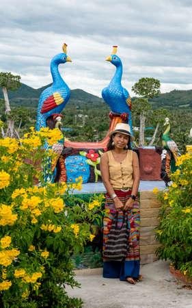 Woman standing in garden in wat in Pak Nam pran surrounded by flowers