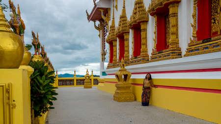woman in sarong leaning against wall of wat in Pak Nam Pran Pranburi Thailand.
