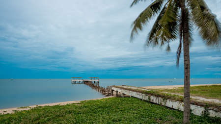 palm tree and walkway leading to Dilapidated old fishing dock collapsing into the sea in Pak Nam Pran on the Gulf of Thailand in Thailand