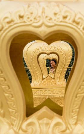 Thai woman framed by multiple gold hearts in wat in Pak Nam Pran