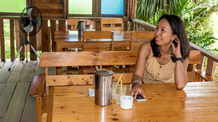 Woman sitting at table in cafe holding cell phone and smiling in Pak Nam Pran pranburi Thailand