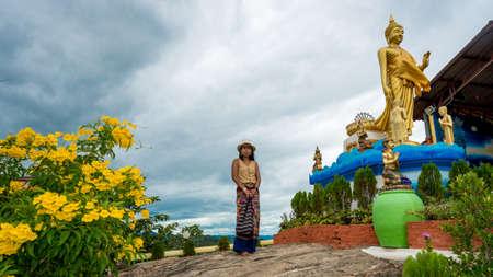 Woman standing in garden in wat in Pak Nam pran surrounded by flowers Reklamní fotografie