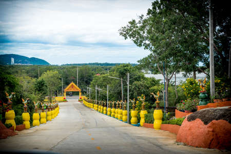 Entrance to wat lined with statues on yellow pedestals in Pak Nam Pran, Pranburi Thailand