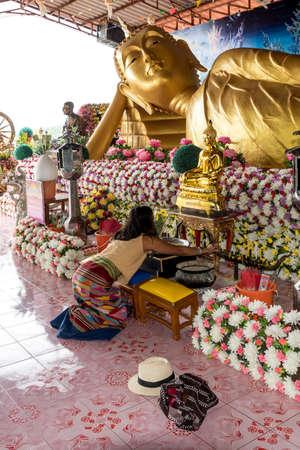 Woman praying in wat to reclining Buddha surrounded by flowers in Pak Nam Pran, Thailand