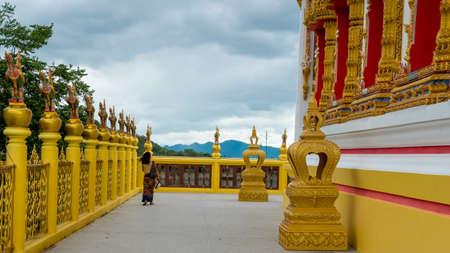 woman in sarong walking along wall of wat in Pak Nam Pran Pranburi Thailand.