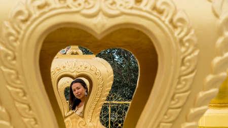 Thai woman framed by multiple gold hearts in wat in Pak Nam Pran Reklamní fotografie