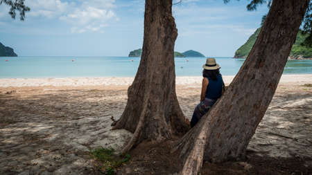Woman with white fedora and sarong leaning against tree at the beach looking at the sea in Khao Lommuak thailand 免版税图像