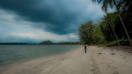 woman in white fedora hat and sarong sown the beach with palm trees and storm clouds in the background in Khao Lommuak Thailand
