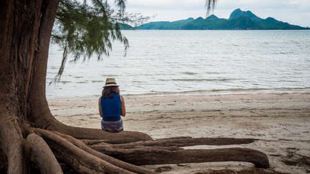 Woman sitting on large tree roots on the beach looking at her phone in Khoa Lommuak thailand