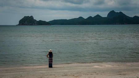 woman in white fedora hat and sarong standing on the beach with islands in the background in Khao Lommuak Thailand