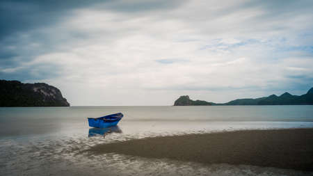 Blue fishing boat sitting in the sand at low tide with islands and blue sky in the background in Khao Lummuak 免版税图像