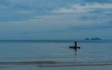 Older man fishing on smal traditional boat in calm seas on the Gulf of Thailand 免版税图像