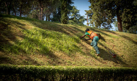 Workman in green pants and orange vest climbing up small hill in orange vest in Bologna, Italy 免版税图像