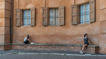 Mother and daughter sitting on brick bench in front of beautiful terracota plastered wall in Bologna Italy