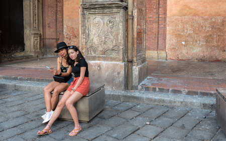 Mother and daughter with red shorts sitting on bench on road looking at photographer while holding cell phone in Balonga Italy 免版税图像