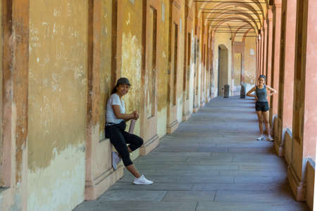 Mother in hat leaning against the wall with thermos in her hand while teen daughter looks at her with hands on her hips in Bologna Italy 免版税图像