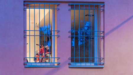 Red motorcycle behind blue bars on a purple building in Bologna Italy