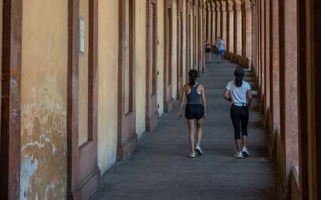 Mother and daughter running for exercise in portico in Bolgona Italy 免版税图像