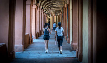 Mother in black hat and daughter walking down promanade in sneakers and shorts and pants in Bologna Italy